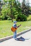 Chłopiec bawić się na gitarze akustycznej outdoors Mały uliczny muzyk KYIV UKRAINA Maj 01, 2016 Zdjęcia Royalty Free