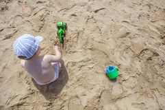Chłopiec bawić się na piasku przy plażą z zabawkarskim backhoe i wodą Zdjęcia Stock