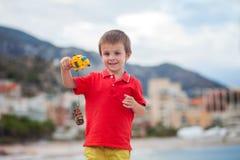 Chłopiec, bawić się na plaży w wieczór po deszczu z zabawkami Fotografia Royalty Free