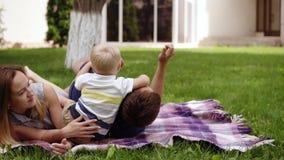 Chłopiec bawić się outdoors z jego rodzicami Ojciec i matka odpoczynek na ziemi, pinkin Syn jest na ojcach zdjęcie wideo