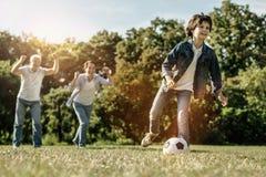 Chłopiec bawić się piłkę i jego rodzinnego zachęcanie on obrazy stock