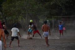 CHŁOPIEC bawić się piłkę nożną przy zmierzchem na drzewka palmowego polu blisko plaży Gil ASAHAN INDONEZJA, SIERPIEŃ -, 22 2016 - Zdjęcie Royalty Free