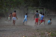 CHŁOPIEC bawić się piłkę nożną przy zmierzchem na drzewka palmowego polu blisko plaży Gil ASAHAN INDONEZJA, SIERPIEŃ -, 22 2016 - Zdjęcie Stock