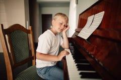 Chłopiec bawić się pianino w domu Zdjęcia Royalty Free