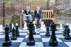 Chłopiec bawić się plenerowego szachy Zdjęcia Royalty Free