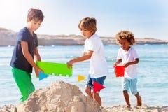 Chłopiec bawić się przy nadmorski i robi sandcastle zdjęcia royalty free