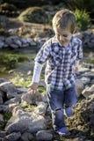 Chłopiec bawić się przy rzeką Zdjęcie Royalty Free