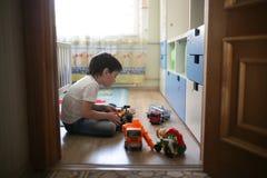 Chłopiec bawić się samotnie w pokoju, samotność Obraz Royalty Free