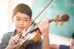 Chłopiec bawić się skrzypce w muzycznej klasie i ćwiczą Fotografia Royalty Free