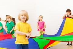Chłopiec bawić się spadochron z przyjaciółmi w dziecinu obraz stock
