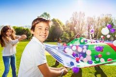 Chłopiec bawić się spadochron z przyjaciółmi w lato parku obraz stock