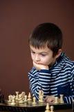 Chłopiec, bawić się szachy Mądrze dzieciak bawić się szachy, Zdjęcia Royalty Free