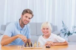 Chłopiec bawić się szachy z jego ojcem Obrazy Stock