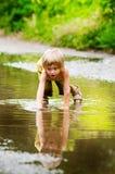 Chłopiec bawić się w kałuży obraz stock