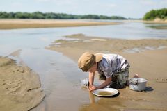 Chłopiec bawić się w piasku na bankach rzeka zdjęcia royalty free