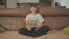 Chłopiec bawić się wideo gry na konsoli dalej kanapa w domu zbiory