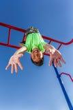 Chłopiec bawić się wiesza do góry nogami podczas gdy obraz royalty free