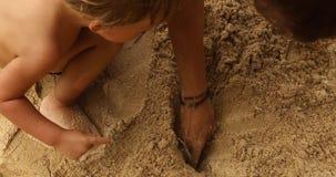 Chłopiec bawić się z beztwarzowym rodzicem na piaskowatej plaży zbiory wideo