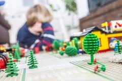 Chłopiec bawić się z cegłami na podłoga obrazy stock