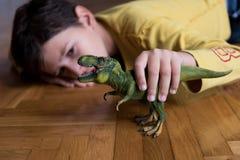 Chłopiec bawić się z dinosaurem Zdjęcia Stock