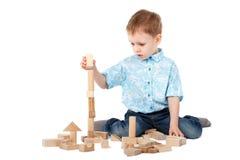 Chłopiec bawić się z drewnianym projektantem na podłoga Obrazy Stock