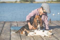 Chłopiec bawić się z jego pies i kot rzeką obrazy stock