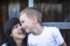 Chłopiec bawić się z jego starą siostrą wewnątrz outdoors rodzina fotografia stock