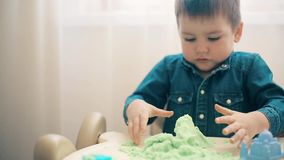 Chłopiec bawić się z kinetycznym piaskiem i rozwija motorowe umiejętności ręki zbiory wideo