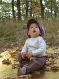 Chłopiec bawić się z liśćmi przy złotym jesień parka tłem Zdjęcie Royalty Free