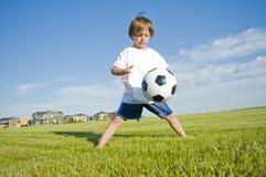 Chłopiec bawić się z piłką Zdjęcia Royalty Free