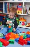 Chłopiec bawić się z plastikowymi blokami Zdjęcia Royalty Free
