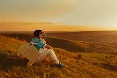Chłopiec bawić się z samolotem na naturze przy zmierzchem obraz royalty free