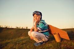 Chłopiec bawić się z samolotem na naturze przy zmierzchem zdjęcia stock