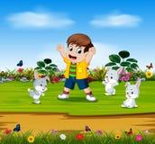 Chłopiec bawić się z trzy królikami w ogródzie royalty ilustracja