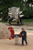 Chłopiec bawić się z wiosny huśtawką z dinosaurem w backgroung Fotografia Stock