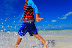 Chłopiec bawić się z wodą na lato plaży Fotografia Stock