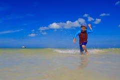 Chłopiec bawić się z wodą na lato plaży Zdjęcia Stock