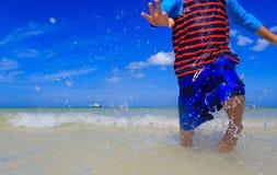 Chłopiec bawić się z wodą na lato plaży Zdjęcie Stock