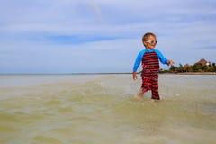 Chłopiec bawić się z wodą na lato plaży Zdjęcie Royalty Free