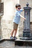 Chłopiec bawić się z wody pitnej fontanną w Włochy Zdjęcia Stock