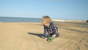 Chłopiec bawić się z zabawkarską zieloną usyp ciężarówką na plaży zbiory