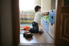 Chłopiec bawić się z zabawkarskimi samochodami w dziecka ` s pokoju Zdjęcia Royalty Free
