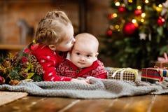 Chłopiec berbeć w czerwonym pulowerze całuje jego starej siostry, lyi obraz stock
