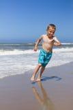 Chłopiec bieg i ono uśmiecha się przy plażą fotografia stock