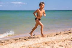 Chłopiec bieg od morza na plaży Obrazy Royalty Free