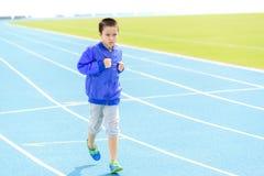 Chłopiec bieg w błękita śladzie Obrazy Stock