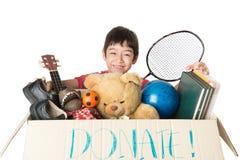 Chłopiec bierze darowiźnie pudełkowaty pełnego z materiałem dla daruje obrazy royalty free