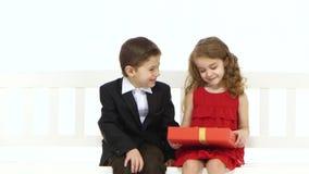 Chłopiec bierze parę spodnia i daje dziewczyny w powrocie całuje on na policzku Biały tło zbiory wideo