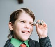 Chłopiec biznesmena spojrzenia przez małej tubki od dolara obraz stock