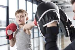 Chłopiec boksera ćwiczy poncze z trenerem Zdjęcie Royalty Free